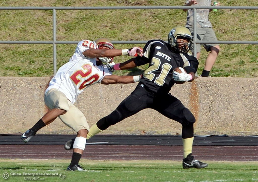 Description of . Butte College's #21 Marvel Harris (right) is pushed out of bounds against De Anza College's 320 Kyree Rhodes (left) in the third quarter of their football game at Butte's Cowan Stadium Saturday, October 26, 2013 in Oroville, Calif.  (Jason Halley/Chico Enterprise-Record)