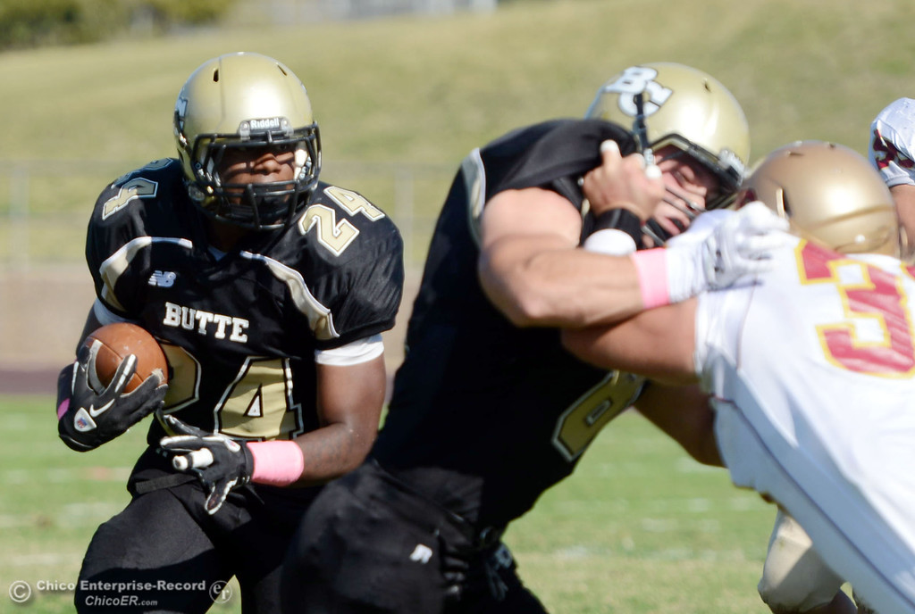 Description of . Butte College\'s #24 Kendall Williams (left) rushes on a block by #8 Bo Brummel (center) against De Anza College\'s #33 Chuck Sullivan (right) in the second quarter of their football game at Butte\'s Cowan Stadium Saturday, October 26, 2013 in Oroville, Calif.  (Jason Halley/Chico Enterprise-Record)
