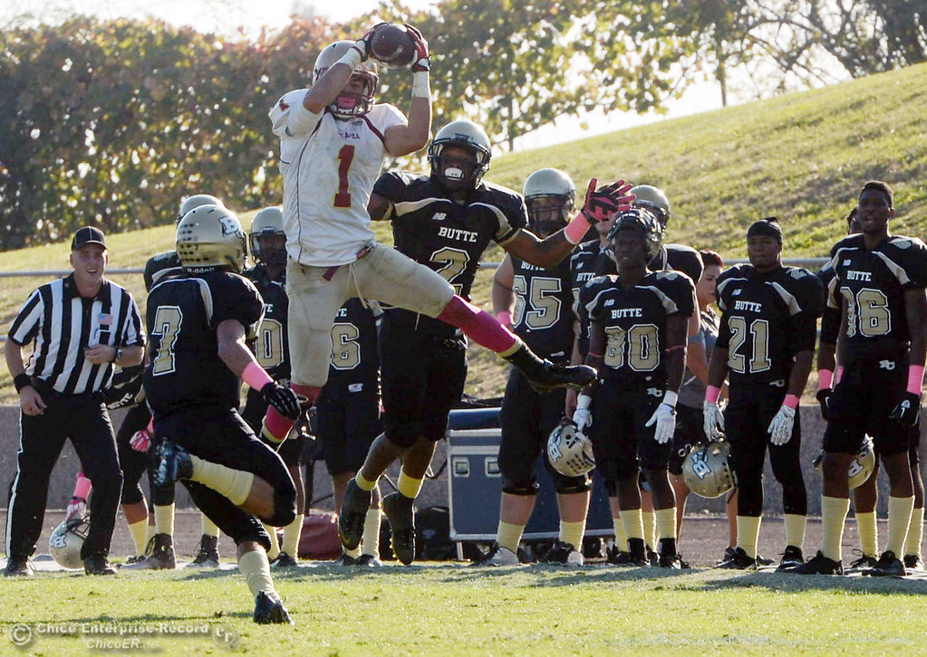 Description of . Butte College's #7 Ryan Holland (left) and #2 Deonte Flemings (right) watch against De Anza College's #1 Bryan Fobbs (center) complete a catch in the fourth quarter of their football game at Butte's Cowan Stadium Saturday, October 26, 2013 in Oroville, Calif.  (Jason Halley/Chico Enterprise-Record)