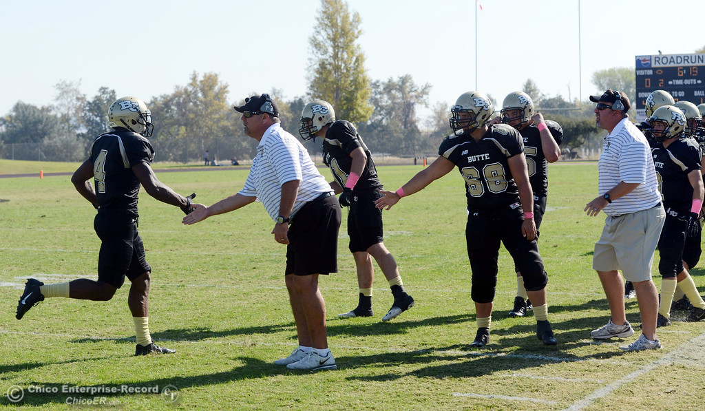 Description of . Butte College coaches WIllie Thomas (left) and Jeff Jordan (right) congratulate the defense against De Anza College in the second quarter of their football game at Butte's Cowan Stadium Saturday, October 26, 2013 in Oroville, Calif.  (Jason Halley/Chico Enterprise-Record)
