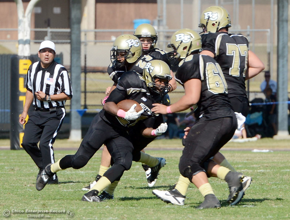 Description of . Butte College's #21 Marvel Harris (center) rushes against De Anza College in the second quarter of their football game at Butte's Cowan Stadium Saturday, October 26, 2013 in Oroville, Calif.  (Jason Halley/Chico Enterprise-Record)