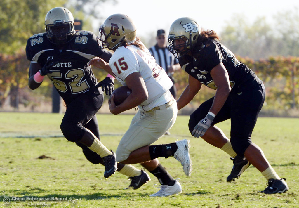 Description of . Butte College's #52 Kyjuan Tate (left) and #99 Leopeni Siania (right) tackle against De Anza College's #15 Paris Shaw (center) in the fourth quarter of their football game at Butte's Cowan Stadium Saturday, October 26, 2013 in Oroville, Calif.  (Jason Halley/Chico Enterprise-Record)
