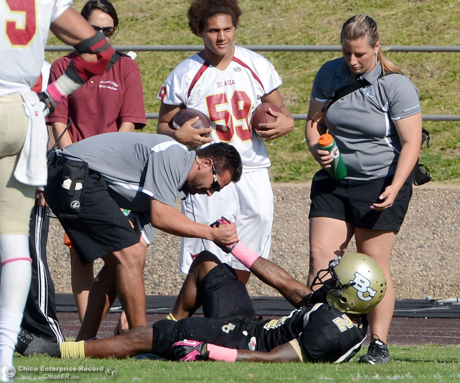 Description of . Butte College's #2 Deonte Flemings (right) is checked on an injury against De Anza College in the second quarter of their football game at Butte's Cowan Stadium Saturday, October 26, 2013 in Oroville, Calif.  (Jason Halley/Chico Enterprise-Record)