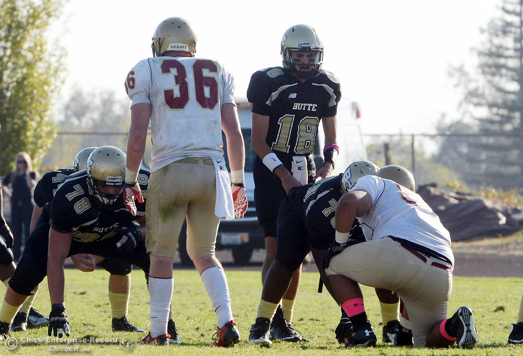 Description of . Butte College's #18 Eric Ascensio readies the snap against De Anza College in the fourth quarter of their football game at Butte's Cowan Stadium Saturday, October 26, 2013 in Oroville, Calif.  (Jason Halley/Chico Enterprise-Record)