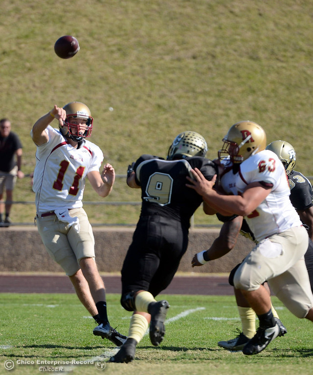Description of . Butte College's #9 Tyler Adair (center) pressures against De Anza College's #11 Jack Singler (left) on a pass in the first quarter of their football game at Butte's Cowan Stadium Saturday, October 26, 2013 in Oroville, Calif.  (Jason Halley/Chico Enterprise-Record)
