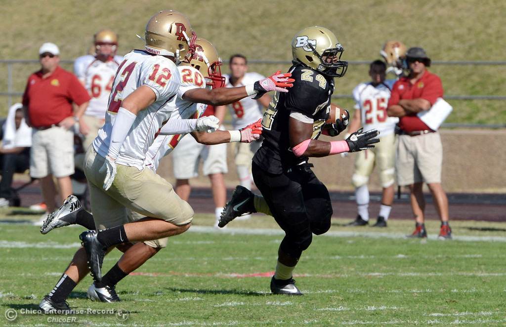 Description of . Butte College's #24 Kendall Williams (right) rushes against De Anza College's #20 Kyree Rhodes (cener) and #12 Rodney McKenzie (left) in the second quarter of their football game at Butte's Cowan Stadium Saturday, October 26, 2013 in Oroville, Calif.  (Jason Halley/Chico Enterprise-Record)