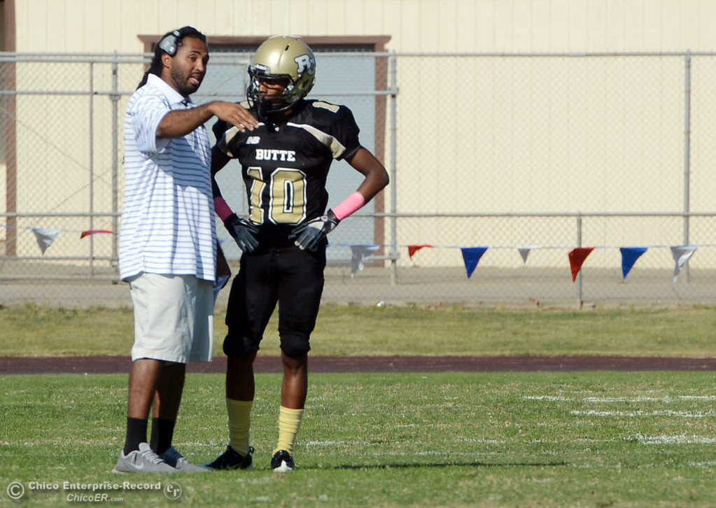 Description of . Butte College coach Bobby Bernal (left) talks to #10 CJ Grice (right) against De Anza College in the second quarter of their football game at Butte\'s Cowan Stadium Saturday, October 26, 2013 in Oroville, Calif.  (Jason Halley/Chico Enterprise-Record)