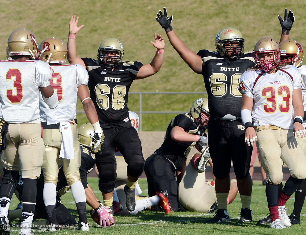Description of . Butte College\'s #68 Eli Thom (center) and #66 Paul Tablit III (right) react to a touchdown by #20 Armand Bokitch (bottom) against De Anza College in the third quarter of their football game at Butte\'s Cowan Stadium Saturday, October 26, 2013 in Oroville, Calif.  (Jason Halley/Chico Enterprise-Record)