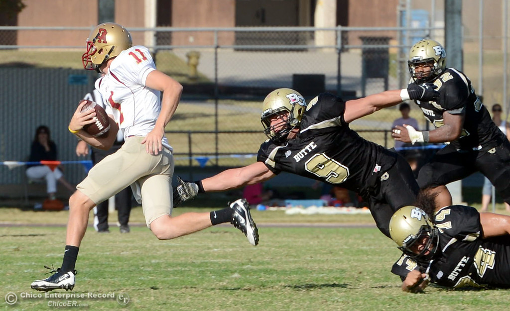 Description of . De Anza College\'s #11 Jack Singler (left) slips past Butte College #9 Tyler Adair (right) in the third quarter of their football game at Butte\'s Cowan Stadium Saturday, October 26, 2013 in Oroville, Calif.  (Jason Halley/Chico Enterprise-Record)