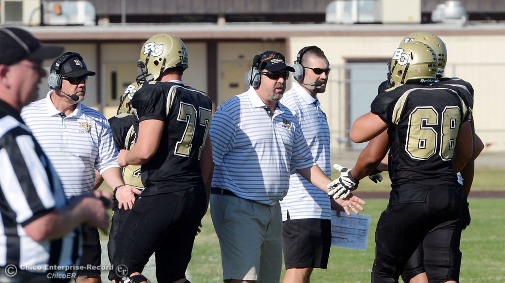 Description of . Butte College coaches Willie Thomas, Jeff Jordan and Rob Snelling (left to right) congratulate #77  Scott Batchelder (left) and #68 Eli Thom (right) against De Anza College in the third quarter of their football game at Butte\'s Cowan Stadium Saturday, October 26, 2013 in Oroville, Calif.  (Jason Halley/Chico Enterprise-Record)