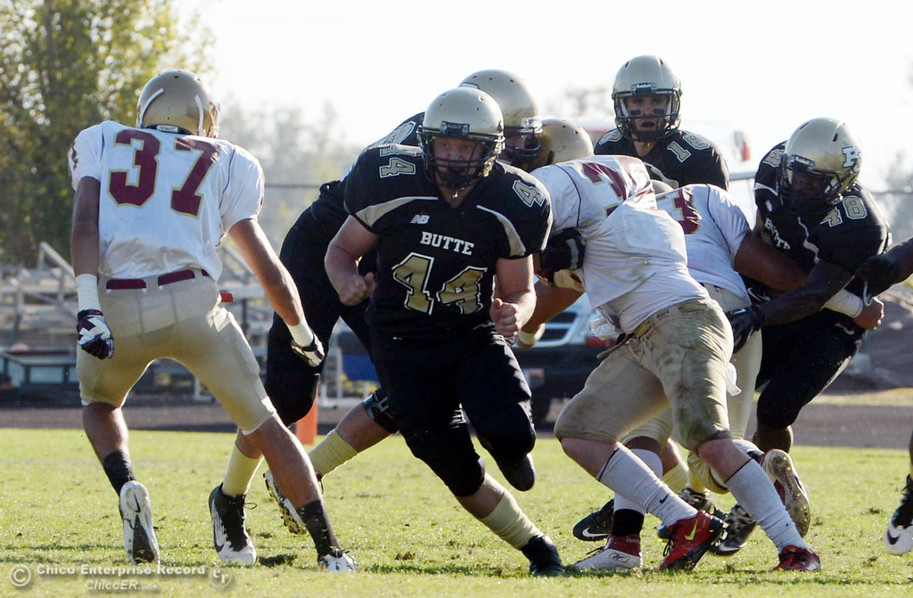 Description of . Butte College\'s #44 Casey Gingerich (center) defends against De Anza College\'s #37 Jeremy Imlach (left) in the fourth quarter of their football game at Butte\'s Cowan Stadium Saturday, October 26, 2013 in Oroville, Calif.  (Jason Halley/Chico Enterprise-Record)