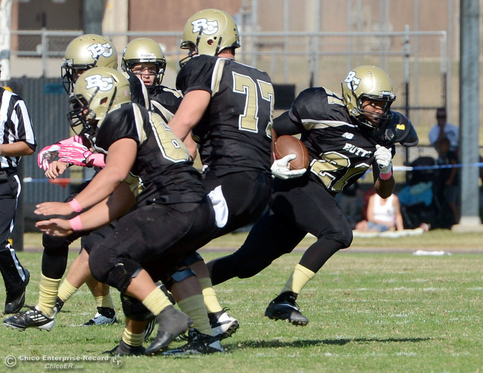 Description of . Butte College\'s #21 Marvel Harris (center) rushes against De Anza College in the second quarter of their football game at Butte\'s Cowan Stadium Saturday, October 26, 2013 in Oroville, Calif.  (Jason Halley/Chico Enterprise-Record)