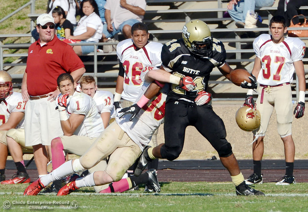Description of . Butte College\'s #24 Kendall Williams (right) is tackled against De Anza College\'s #36 Brandon Martinez (left) in the third quarter of their football game at Butte\'s Cowan Stadium Saturday, October 26, 2013 in Oroville, Calif.  (Jason Halley/Chico Enterprise-Record)