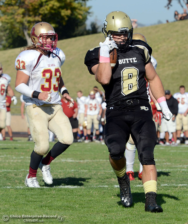 Description of . Butte College\'s #8 Bo Brummel (right) scores a touchdown against De Anza College\'s #33 Chuck Sullivan (left) in the third quarter of their football game at Butte\'s Cowan Stadium Saturday, October 26, 2013 in Oroville, Calif.  (Jason Halley/Chico Enterprise-Record)