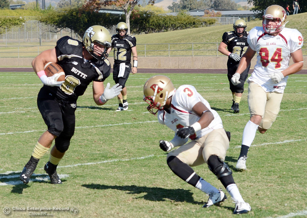 Description of . Butte College\'s #8 Bo Brummel (left) rushes against De Anza College\'s #3 Johnny Beard (right) in the second quarter of their football game at Butte\'s Cowan Stadium Saturday, October 26, 2013 in Oroville, Calif.  (Jason Halley/Chico Enterprise-Record)