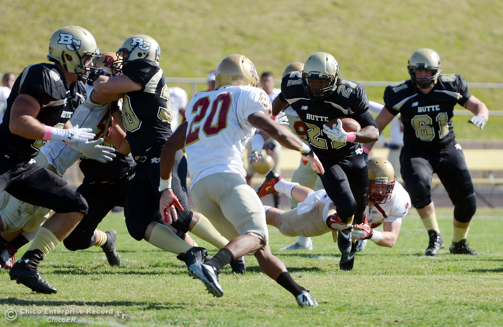 Description of . Butte College's #21 Marvel Harris (right) rushes against De Anza College in the first quarter of their football game at Butte's Cowan Stadium Saturday, October 26, 2013 in Oroville, Calif.  (Jason Halley/Chico Enterprise-Record)