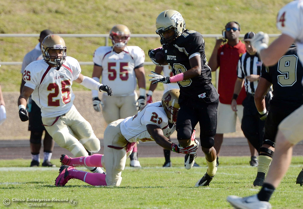 Description of . Butte College's #10 CJ Grice (right) breaks a tackle against De Anza College's #23 Tyler Bond (left) in the first quarter of their football game at Butte's Cowan Stadium Saturday, October 26, 2013 in Oroville, Calif.  (Jason Halley/Chico Enterprise-Record)