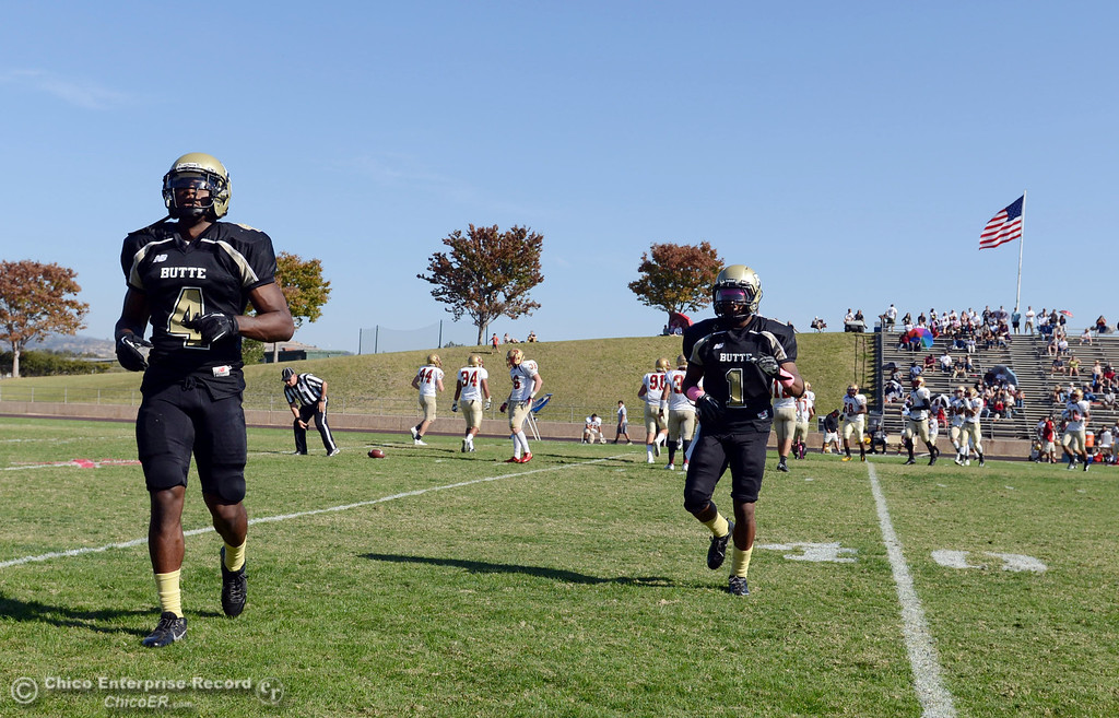 Description of . Butte College's #4  Chris Edwards (left) and #1 Wes McCoy (right) come off the field against De Anza College in the second quarter of their football game at Butte's Cowan Stadium Saturday, October 26, 2013 in Oroville, Calif.  (Jason Halley/Chico Enterprise-Record)