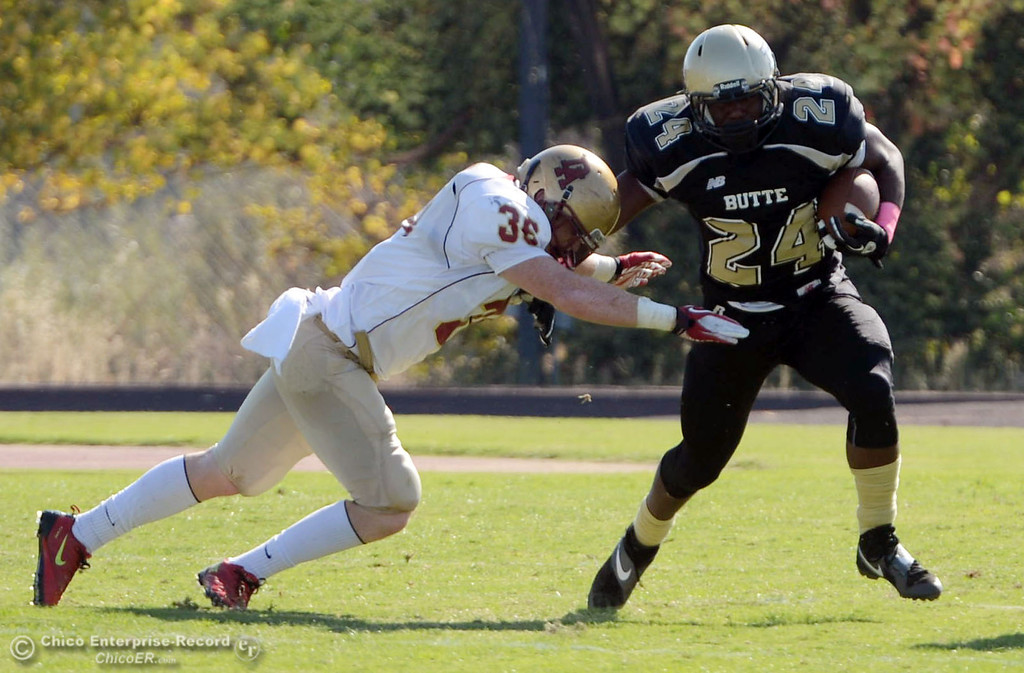 Description of . Butte College's #24 Kendall Williams (right) rushes against De Anza College's #36 Brandon Martinez (left) in the first quarter of their football game at Butte's Cowan Stadium Saturday, October 26, 2013 in Oroville, Calif.  (Jason Halley/Chico Enterprise-Record)
