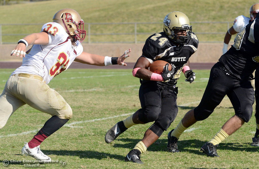 Description of . Butte College\'s #24 Kendall Williams (right) rushes against De Anza College\'s #33  Chuck Sullivan (left) in the second quarter of their football game at Butte\'s Cowan Stadium Saturday, October 26, 2013 in Oroville, Calif.  (Jason Halley/Chico Enterprise-Record)