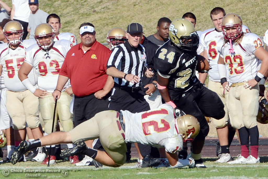 Description of . Butte College's #24 Kendall Williams (top) breaks a tackle against De Anza College's #12 Rodney McKenzie (bottom) in the third quarter of their football game at Butte's Cowan Stadium Saturday, October 26, 2013 in Oroville, Calif.  (Jason Halley/Chico Enterprise-Record)