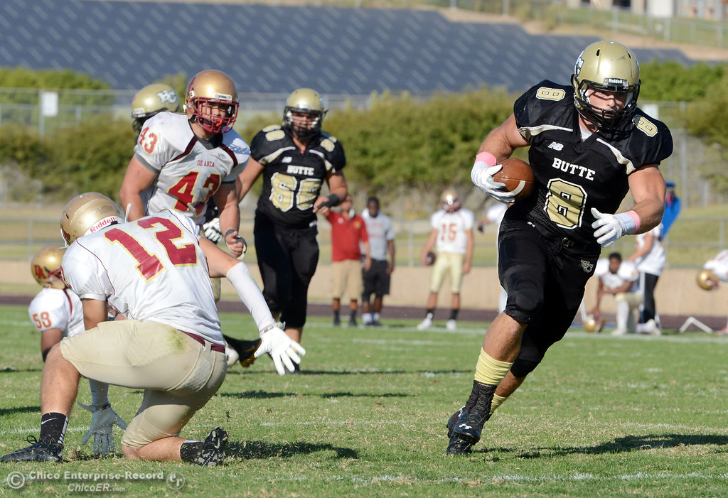 Description of . Butte College\'s #8 Bo Brummel (right) breaks a tackle against De Anza College\'s #12 Rodney McKenzie (left) in the third quarter of their football game at Butte\'s Cowan Stadium Saturday, October 26, 2013 in Oroville, Calif.  (Jason Halley/Chico Enterprise-Record)