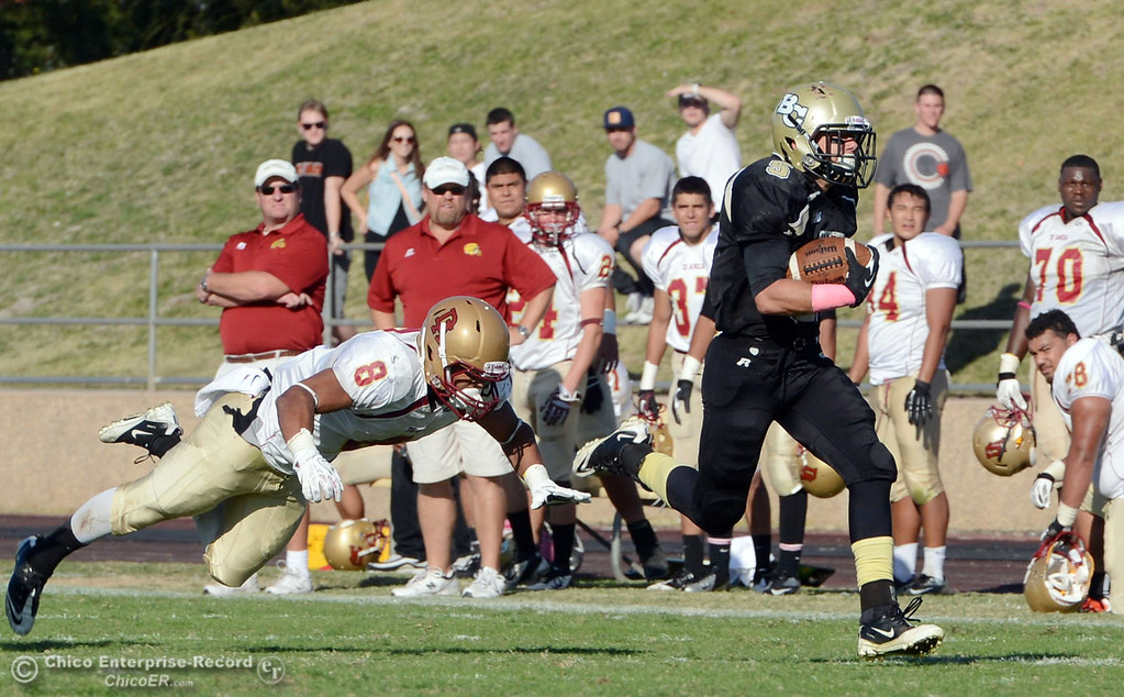 Description of . Butte College\'s #5 David Brannon (right) breaks a tackle to score a touchdown against De Anza College\'s #8 Josh McCain (left)  in the third quarter of their football game at Butte\'s Cowan Stadium Saturday, October 26, 2013 in Oroville, Calif.  (Jason Halley/Chico Enterprise-Record)