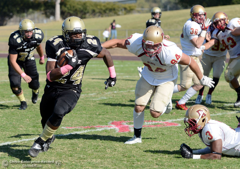 Description of . Butte College's #24 Kendall Williams (left) rushes against De Anza College's #94 Skyler King (center) and #3 Johnny Beard (right) in the second quarter of their football game at Butte's Cowan Stadium Saturday, October 26, 2013 in Oroville, Calif.  (Jason Halley/Chico Enterprise-Record)