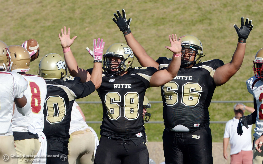 Description of . Butte College's #20 Armand Bokitch (left) scores  a touchdown to be congratulated by #68 Eli Thom (center) and #66 Paul Tablit III (right) against De Anza College in the third quarter of their football game at Butte's Cowan Stadium Saturday, October 26, 2013 in Oroville, Calif.  (Jason Halley/Chico Enterprise-Record)