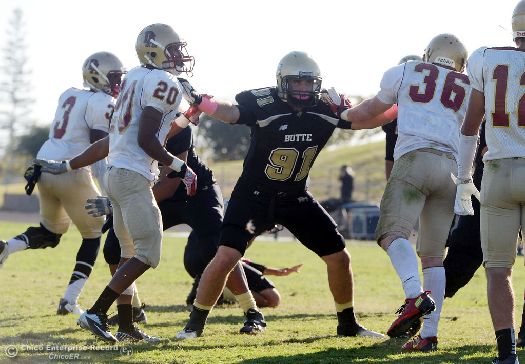 Description of . Butte College's #91 Mike Fratianni (center) defends on the extra point kick against De Anza College's #20 Kyree Rhodes (left) and #36 Brandon Martinez (right) in the fourth quarter of their football game at Butte's Cowan Stadium Saturday, October 26, 2013 in Oroville, Calif.  (Jason Halley/Chico Enterprise-Record)