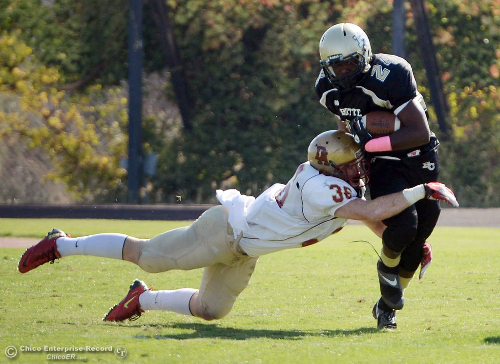 Description of . Butte College\'s #24 Kendall Williams (right) rushes against De Anza College\'s #36 Brandon Martinez (left) in the first quarter of their football game at Butte\'s Cowan Stadium Saturday, October 26, 2013 in Oroville, Calif.  (Jason Halley/Chico Enterprise-Record)