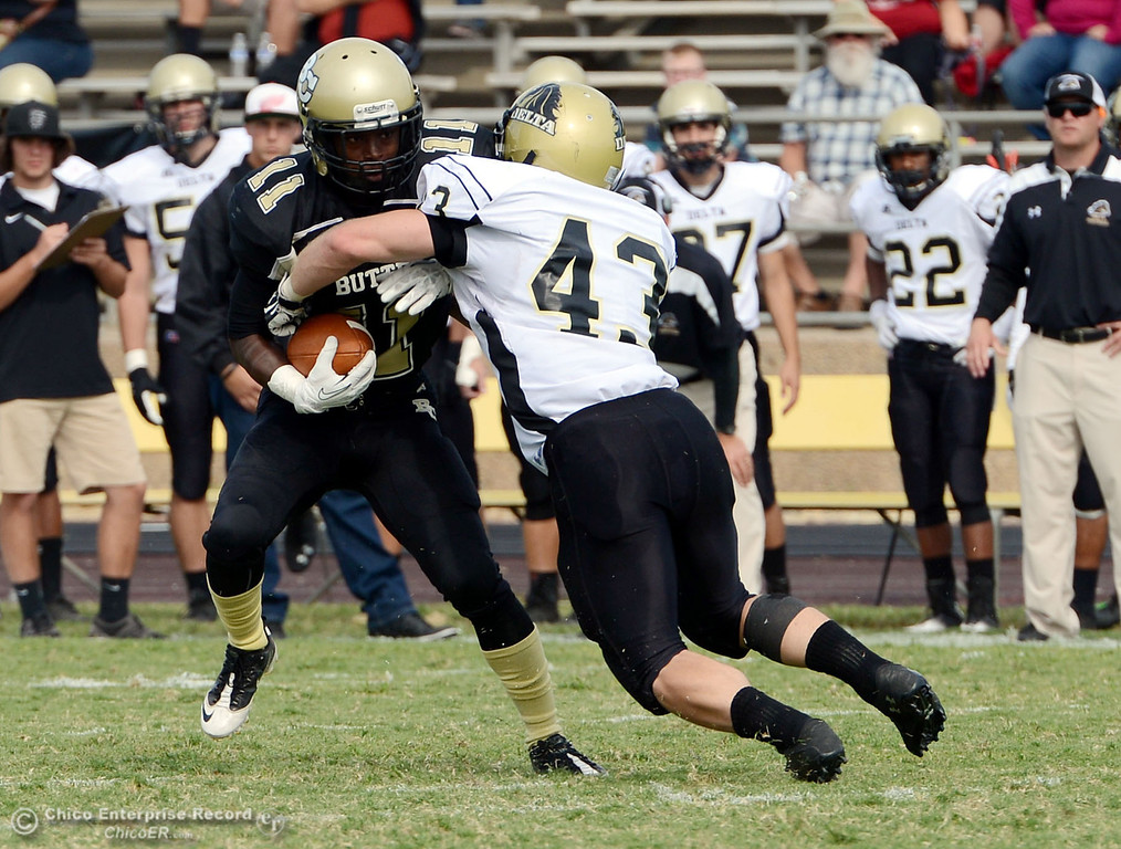 Description of . Butte College's #11 Caleb McCullough (left) rushes against Delta College's #43 James Christopherson (right) in the third quarter of their football game at Butte's Cowan Stadium Saturday, September 28, 2013, in Oroville, Calif.  (Jason Halley/Chico Enterprise-Record)