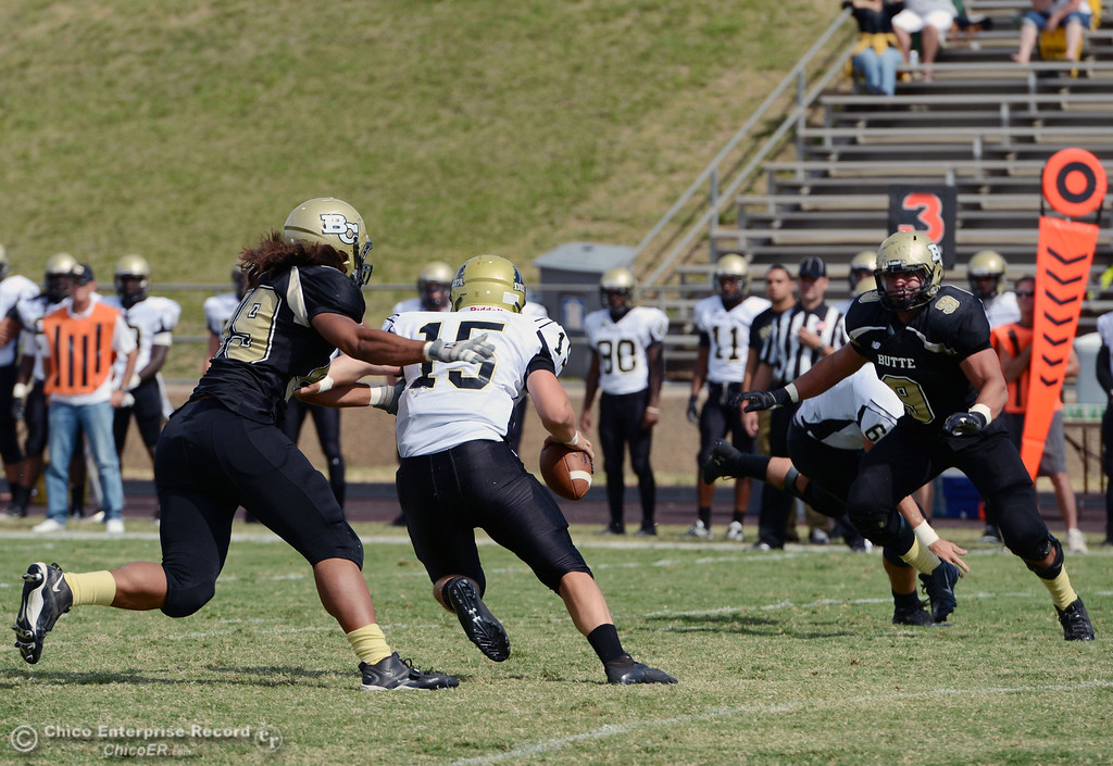 Description of . Butte College\'s #99 Leopeni Siania (left) and #9 Tyler Adair (right) sack against Delta College\'s #15 Cody Weinzheimer (center) in the second quarter of their football game at Butte\'s Cowan Stadium Saturday, September 28, 2013, in Oroville, Calif.  (Jason Halley/Chico Enterprise-Record)