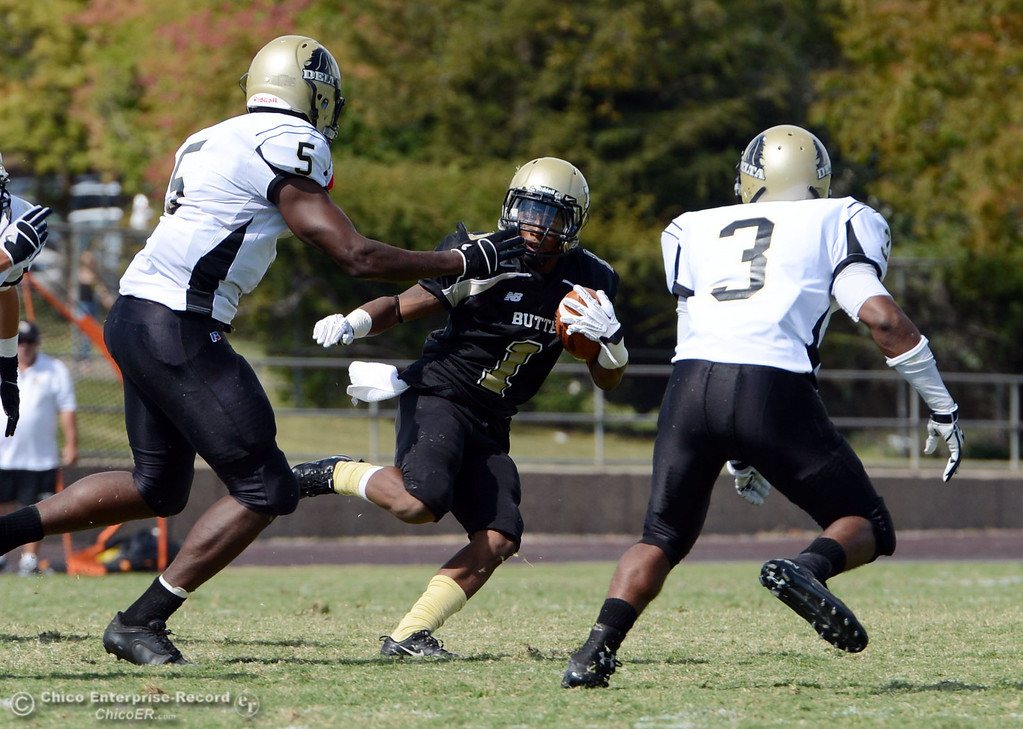 Description of . Butte College's #1 Wes McCoy (center) rushes against Delta College's #5 DaShaun Perkins (left) and #3 SynJohn Sears (right) in the second quarter of their football game at Butte's Cowan Stadium Saturday, September 28, 2013, in Oroville, Calif.  (Jason Halley/Chico Enterprise-Record)