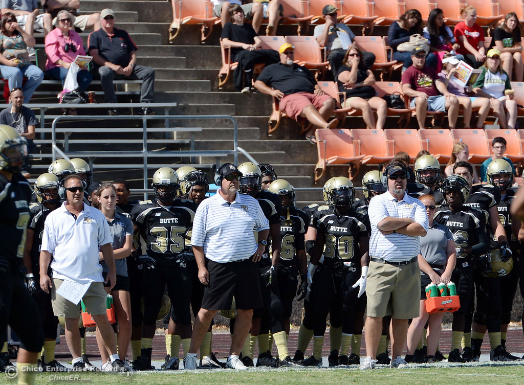 Description of . Butte College coaches Tim Garcia (left) Willie Thomas (center) and Jeff Jordan (right against Delta College in the first quarter of their football game at Butte's Cowan Stadium Saturday, September 28, 2013, in Oroville, Calif.  (Jason Halley/Chico Enterprise-Record)