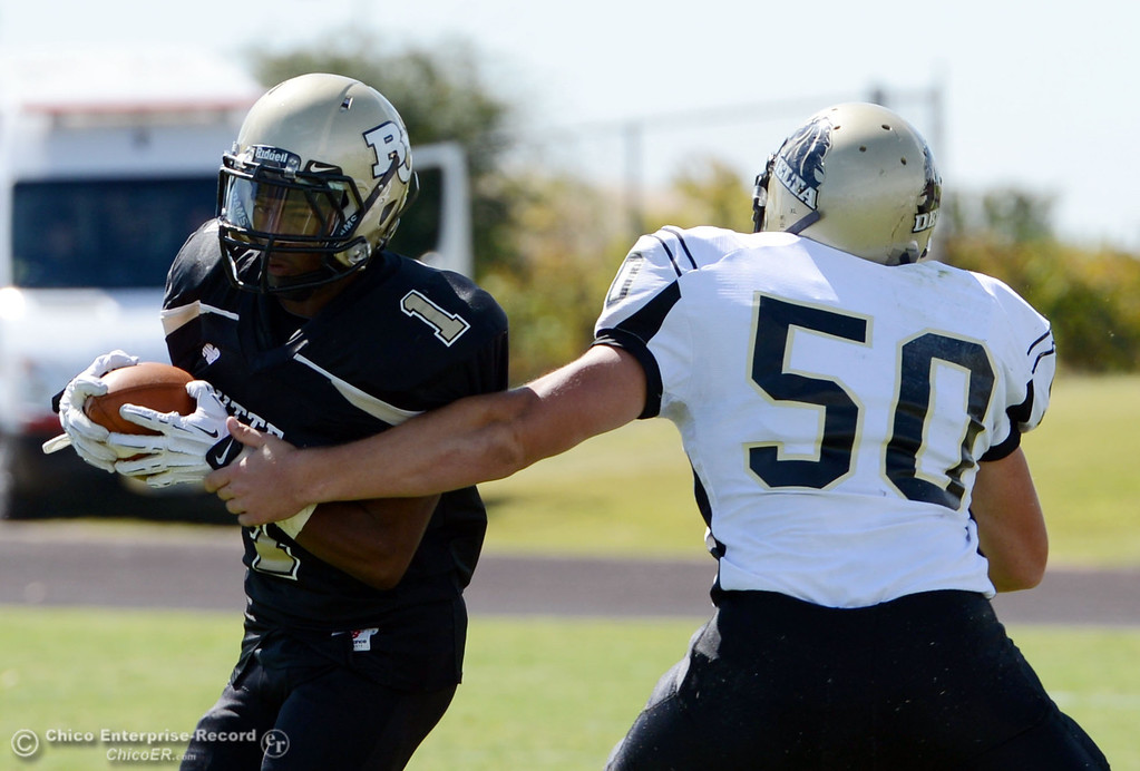 Description of . Butte College\'s #1 Wes McCoy (left) rushes against Delta College\'s #50 Tyler Huckaby (right) in the first quarter of their football game at Butte\'s Cowan Stadium Saturday, September 28, 2013, in Oroville, Calif.  (Jason Halley/Chico Enterprise-Record)