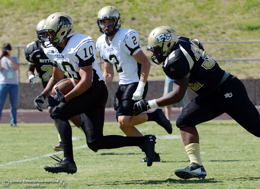Description of . Butte College's #32 Brian Anderson (right) tackles against Delta College's #10 Anthony WIlls (left) in the first quarter of their football game at Butte's Cowan Stadium Saturday, September 28, 2013, in Oroville, Calif.  (Jason Halley/Chico Enterprise-Record)