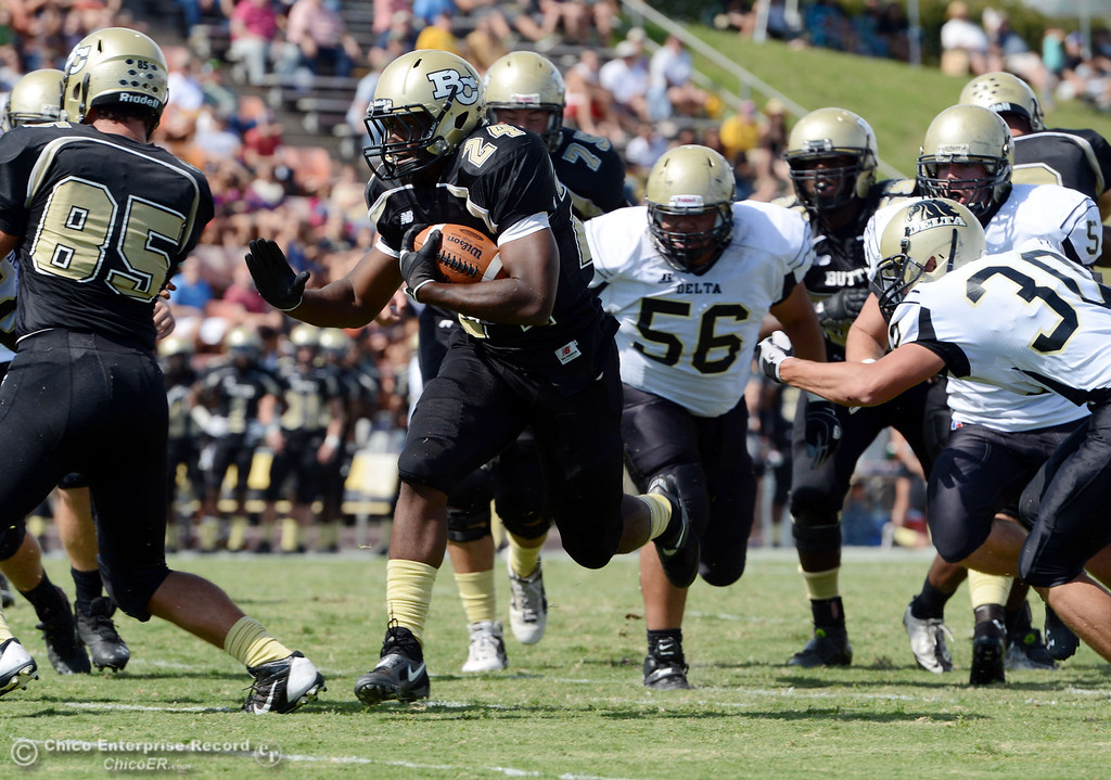 Description of . Butte Colleges' #24 Kendall Williams (left) rushes for a touchdown against Delta College's #56 Sean Casto (center) and #30 Andrew Truax (right) in the second quarter of their football game at Butte's Cowan Stadium Saturday, September 28, 2013, in Oroville, Calif.  (Jason Halley/Chico Enterprise-Record)
