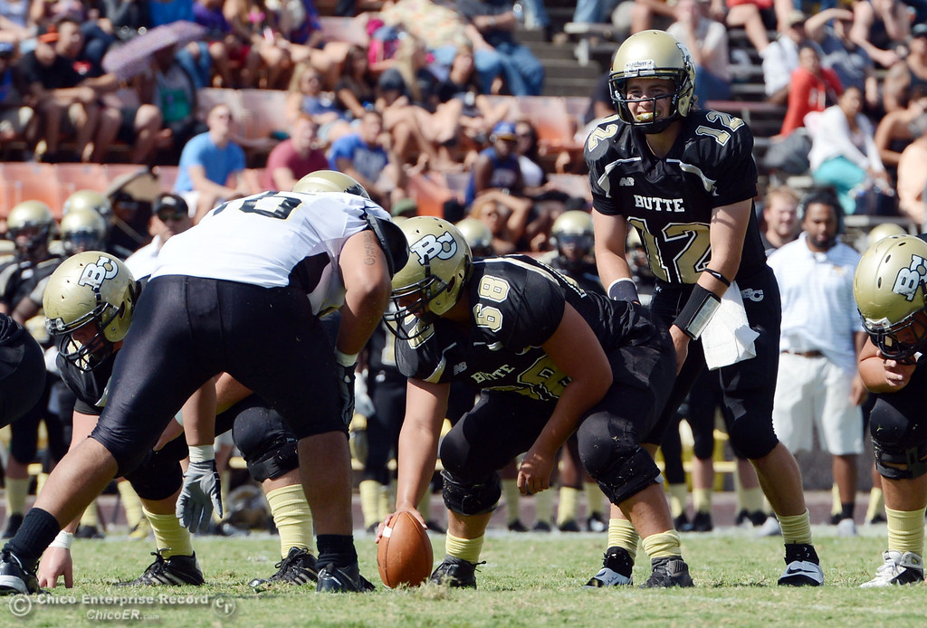 Description of . Butte College's #12 Thomas Stuart (right) readies the snap from #68 Eli Thom (center) against Delta College in the second quarter of their football game at Butte's Cowan Stadium Saturday, September 28, 2013, in Oroville, Calif.  (Jason Halley/Chico Enterprise-Record)