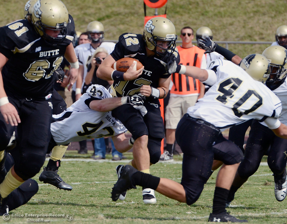 . Butte College\'s #12 Thomas Stuart (center) is tackled against Delta College\'s #53 Noah Schuller (left) in the second quarter of their football game at Butte\'s Cowan Stadium Saturday, September 28, 2013, in Oroville, Calif.  (Jason Halley/Chico Enterprise-Record)