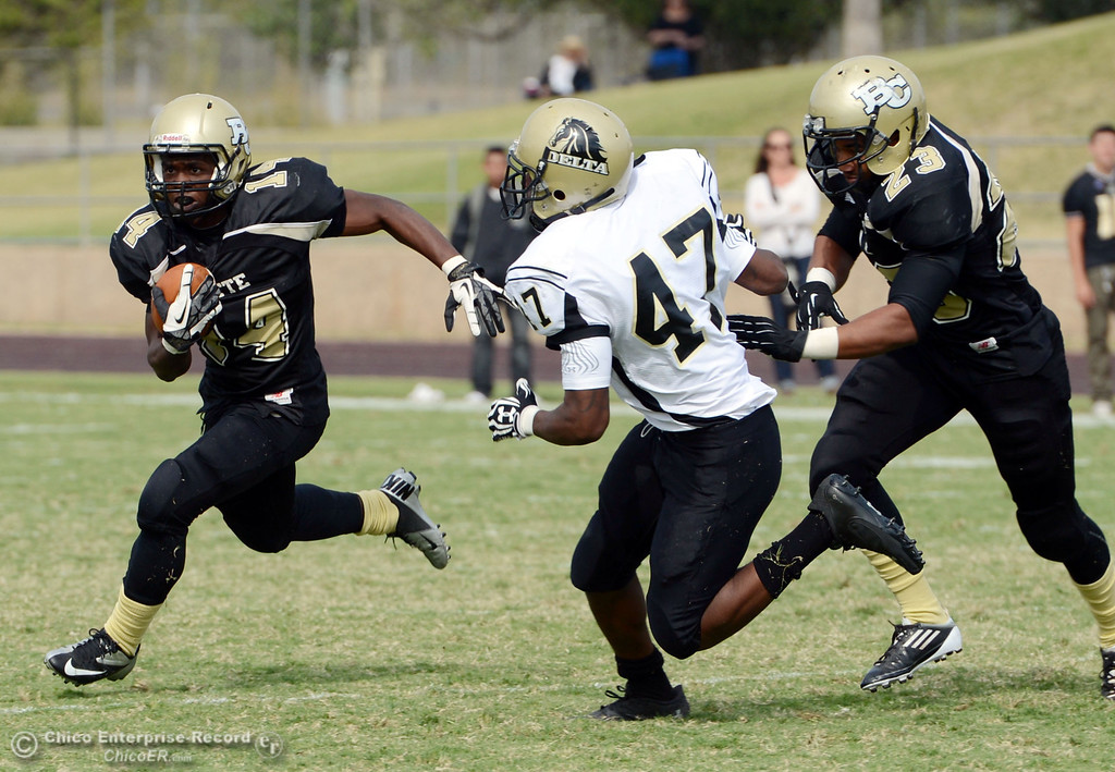 Description of . Butte Colleges' #14 Robert Frazier (left) rushes against Delta College's #47 LeeAndre Fisher (center) on a block by #23 Mykah Hester (right) in the third quarter of their football game at Butte's Cowan Stadium Saturday, September 28, 2013, in Oroville, Calif.  (Jason Halley/Chico Enterprise-Record)