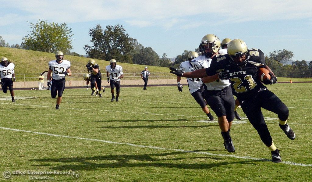 Description of . Butte College's #21 Marvel Harris (right) is tackled against Delta College's #30 Andrew Truax (left) in the fourth quarter of their football game at Butte's Cowan Stadium Saturday, September 28, 2013, in Oroville, Calif.  (Jason Halley/Chico Enterprise-Record)