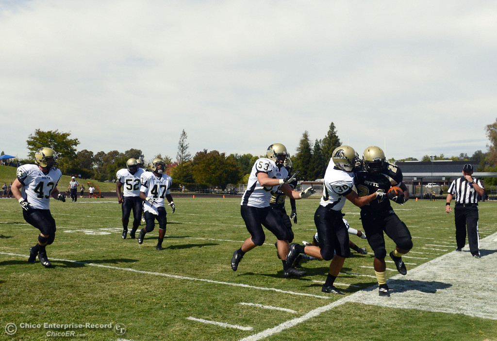 . Butte Colleges\' #24 Kendall Williams (right) rushes against Delta College\'s  #30 Andrew Traux (center) and #53 Noah Schuller (left) in the second quarter of their football game at Butte\'s Cowan Stadium Saturday, September 28, 2013, in Oroville, Calif.  (Jason Halley/Chico Enterprise-Record)