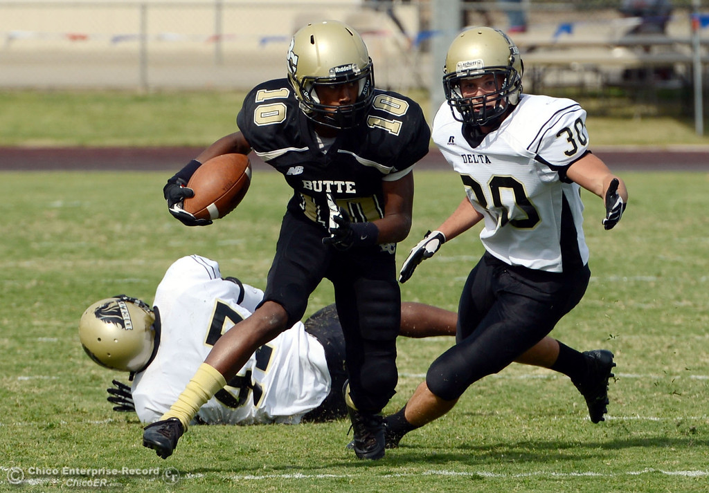 Description of . Butte College's #10 CJ Grice (center) rushes against Delta College's #47 LeeAndre Fisher (left) and #30 Andrew Truaz (right) in the third quarter of their football game at Butte's Cowan Stadium Saturday, September 28, 2013, in Oroville, Calif.  (Jason Halley/Chico Enterprise-Record)