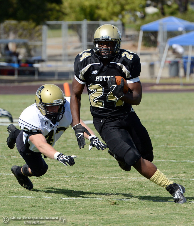 Description of . Butte Colleges' #24 Kendall Williams (right) rushes against Delta College's #43 James Christopherson (left) in the second quarter of their football game at Butte's Cowan Stadium Saturday, September 28, 2013, in Oroville, Calif.  (Jason Halley/Chico Enterprise-Record)