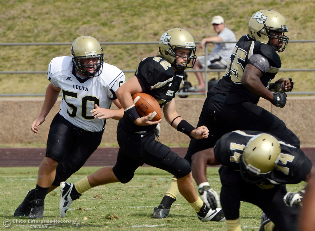 Description of . Butte College's #12 Thomas Stuart (center) scrambles against Delta College's #50 Tyler Huckaby (left) in the second quarter of their football game at Butte's Cowan Stadium Saturday, September 28, 2013, in Oroville, Calif.  (Jason Halley/Chico Enterprise-Record)