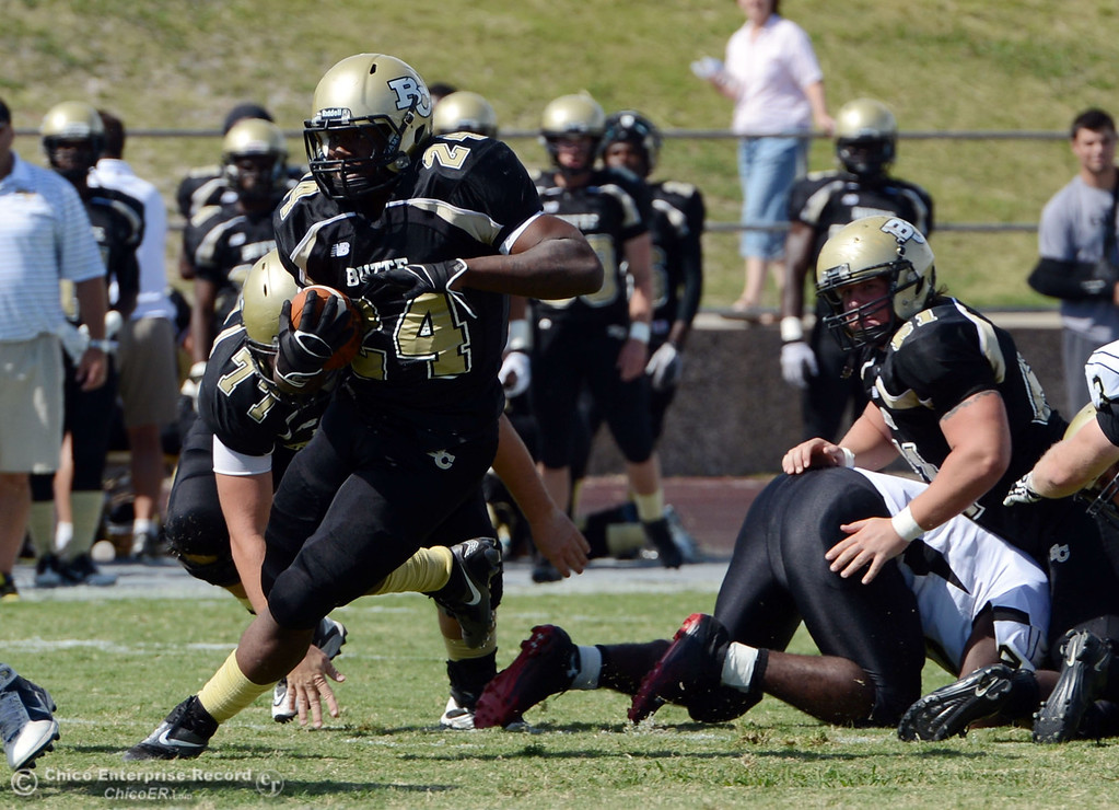 Description of . Butte Colleges' #24 Kendall Williams (left) rushes against Delta College in the second quarter of their football game at Butte's Cowan Stadium Saturday, September 28, 2013, in Oroville, Calif.  (Jason Halley/Chico Enterprise-Record)