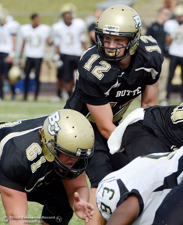 . Butte College\'s #12 Thomas Stuart (top) readies the snap near #61 Jacob Bigham (bottom) against Delta College in the third quarter of their football game at Butte\'s Cowan Stadium Saturday, September 28, 2013, in Oroville, Calif.  (Jason Halley/Chico Enterprise-Record)