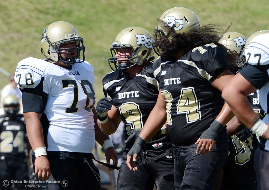 Description of . Butte College\'s #9 Tyler Adair (center) and #74 Christopher Siliga (right) against Delta College\'s #78 Marcelo Hernandez (left) in the first quarter of their football game at Butte\'s Cowan Stadium Saturday, September 28, 2013, in Oroville, Calif.  (Jason Halley/Chico Enterprise-Record)