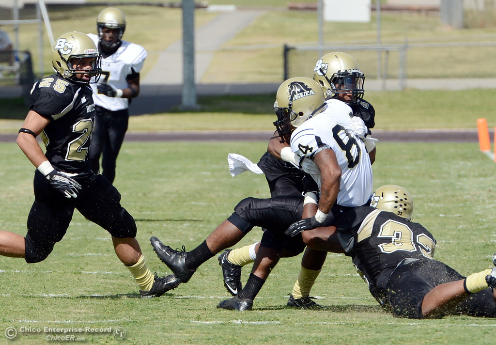 . Delta College\'s #84 Damian Relierford (center) is tackled by Butte Colleges\' #25 De\'Aundray Gooden, #1 Wes McCoy and #32 Brian Anderson (left to right) in the second quarter of their football game at Butte\'s Cowan Stadium Saturday, September 28, 2013, in Oroville, Calif.  (Jason Halley/Chico Enterprise-Record)